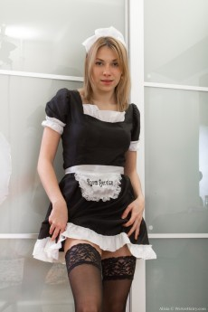 French maid Alisia slowly strips on her bed