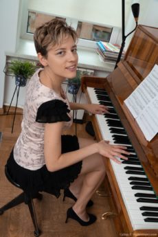 Short haired piano player Calina lifts her skirt to reveal her unshaved gems