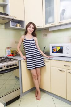 Natural teen Erika plays with her hairy bits in the kitchen
