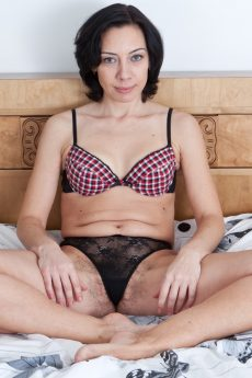 Mature hairy woman Eva pinches her pink puffy nipples