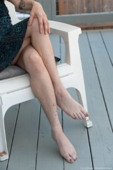 Glasses wearing redhead Ivy Addams strips naked on her outdoor chair