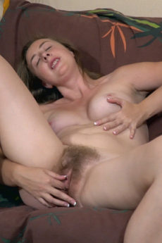 Lucia Siberia strips naked on her brown couch