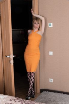 Lovely breasted blonde Natinella removes her orange dress and tights to masturbate